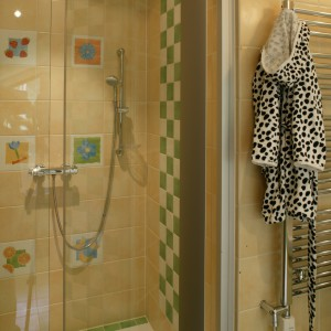 Wnętrze, umieszczonej we wnęce, kabiny prysznicowej powtarza kolorystykę zastosowaną w całej łazience. Frontową ściankę zdobią dwa rzędy wesołych dekorów. Fot. Monika Filipiuk.
