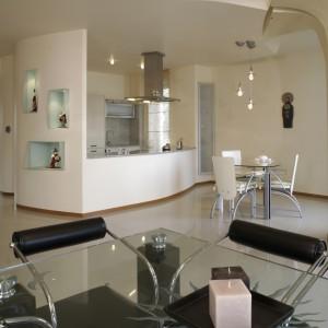 Niewielkiej kuchni towarzyszy przestronna strefa jadalniana. Oddzielne stoły do codziennych posiłków oraz na specjalne okazje, otaczają krzesła ze skórzanymi tapicerkami – dla kontrastu – białą i czarną. Fot. Monika Filipiuk.