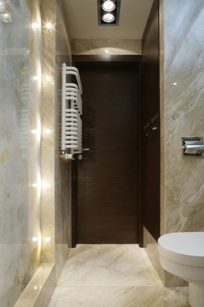 Przedsionek w łazience wyznaczyła bryła szafy gospodarczej. Podświetlona tafla onyksu zdobi ścianę naprzeciw urządzeń sanitarnych. Fot. Monika Filipiuk.
