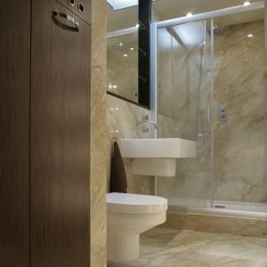 Wąskie wnętrze wymusiło liniowe rozmieszczenie szafy, sedesu i umywalki. Kabina ze szklanymi przesuwnymi drzwiami optycznie skraca długość łazienki. Fot. Monika Filipiuk.