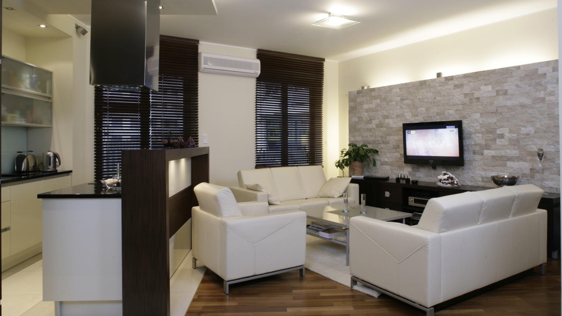 Zarówno salon, jak i kuchnia zostały urządzone w tym samym minimalistycznym stylu – tylko niezbędne sprzęty w prostych, eleganckich liniach. Ciepłą nutę  wprowadza podłoga pokryta akacją parzoną i przesłaniające okna drewniane żaluzje. Fot. Monika Filipiuk.