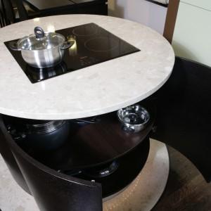 Wyspa to strefa gotowania. W blacie znajduje się płyta ceramiczna, za frontami kryją się półki na akcesoria. Okrągłą bryłę podświetla wąż świetlny umieszczony nad cokołem.  Fot. Monika Filipiuk.