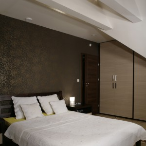 Sypialnia na poddaszu czaruje swoim urokiem. Obudowane i pomalowane na biało (jak cały sufit) belki, doświetlone zostały halogenami. Fot. Monika Filipiuk.