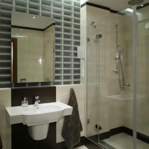 Strefę umywalki wyznaczają ciemne płytki ceramiczne, ułożone na ścianie za nią i podłodze przed nią. Te same płytki opasują też szerokim pasem łazienkę dookoła. Fot. Monika Filipiuk.