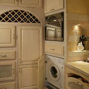 W wysokiej zabudowie zaaranżowano szafki o różnych kształtach i różnym przeznaczeniu (m.in. na kuchenne AGD). Uwagę zwraca dekoracyjny, łukowaty schowek na wino. Fot. Monika Filipiuk.