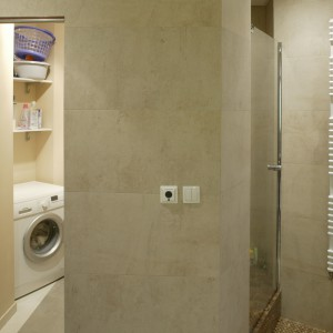 Drzwi do pralni znajdują się tuż przy wejściu do łazienki. Ich kolor został tak dobrany do szarości gresu na ścianach, że naprawdę trudno je zauważyć. Fot. Bartosz Jarosz.