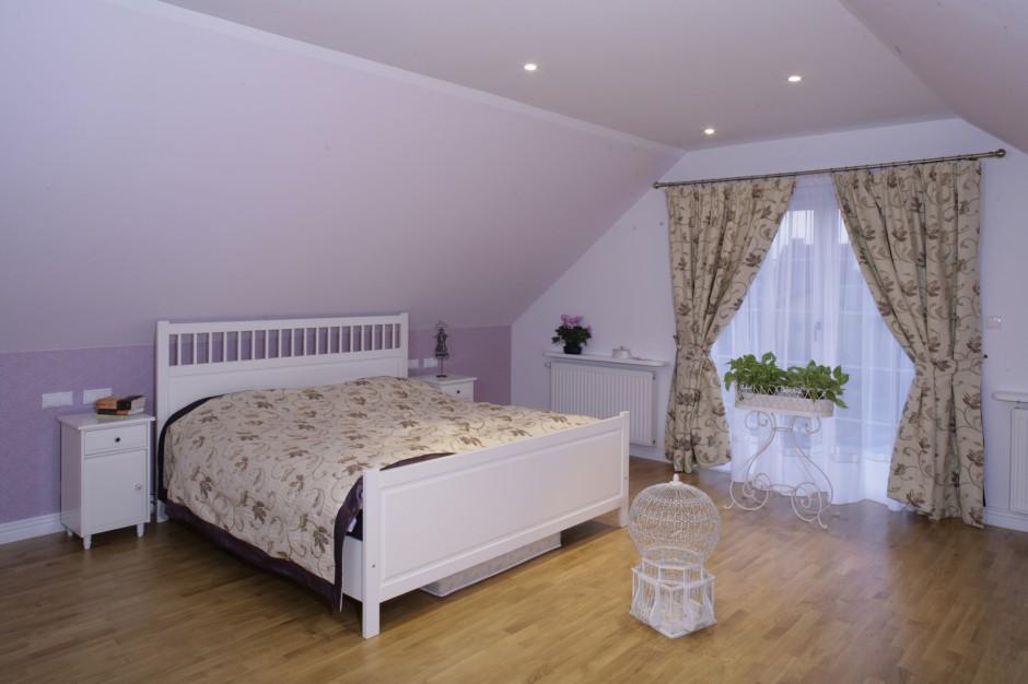 Jasne, duże łóżko i szafeczki nocne (Ikea) doskonale pasują do romantycznej sypialni. Fot. Monika Filipiuk.