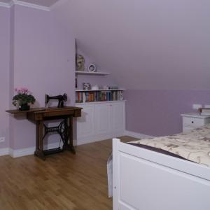 """Podłoga w sypialni wyłożona jest eleganckim, drewnianym parkietem (marka). Jej kolor """" nie kłóci się"""" z wrzosowymi ścianami, a idealnie dopasowany jest do barwy maszyny do szycia. Fot. Monika Filipiuk."""