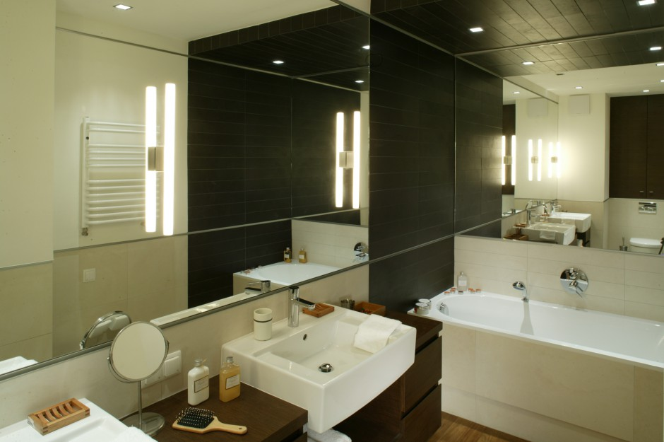 Dwa ogromne lustra, stykające się krawędziami pod kątem prostym, zwielokrotniają przestrzeń łazienki. Im dłużej się przyglądamy, tym trudniej stwierdzić, ile jest w tym wnętrzu kinkietów, umywalek, ścian... Fot. Monika Filipiuk.