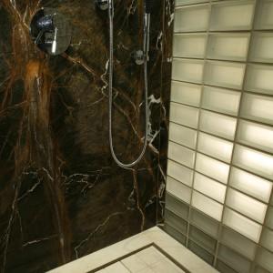 Oryginalny brodzik w kabinie prysznicowej zrobiony został z dwóch płyt marmuru. Woda spływa przez szczeliny wokół jednej z nich. Fot. Bartosz Jarosz.