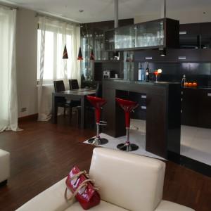 Białe meble w salonie kontrastują z zabudową części kuchennej. Fot. Monika Filipiuk.