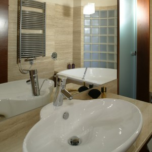 Owalną umywalkę firmy Art Ceram zainstalowano w trawertynowym blacie. W ogromnym lustrze za nią przygląda się cała łazienka. Kosmetyczny rozgardiasz mieści duża szafka pod spodem. Fot. Monika Filipiuk.