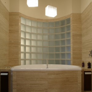"""Wypoczynkową rolę łazienki podkreśla duża wanna (""""Furrora"""", Koło), wpisana w półokrągła ściankę z luksferów, by nie ujmowała przestrzeni. Gra świateł i niebanalne rozwiązania aranżacyjne to definicja luksusu tego wnętrza. Fot. Monika Filipiuk."""