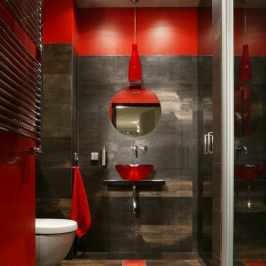 To kolory – czerwień i szarości – decydują o indywidualności i charakterze tej niewielkiej łazienki. Ale nie brak tu także architektonicznych smaczków. Fot. Monika Filipiuk.