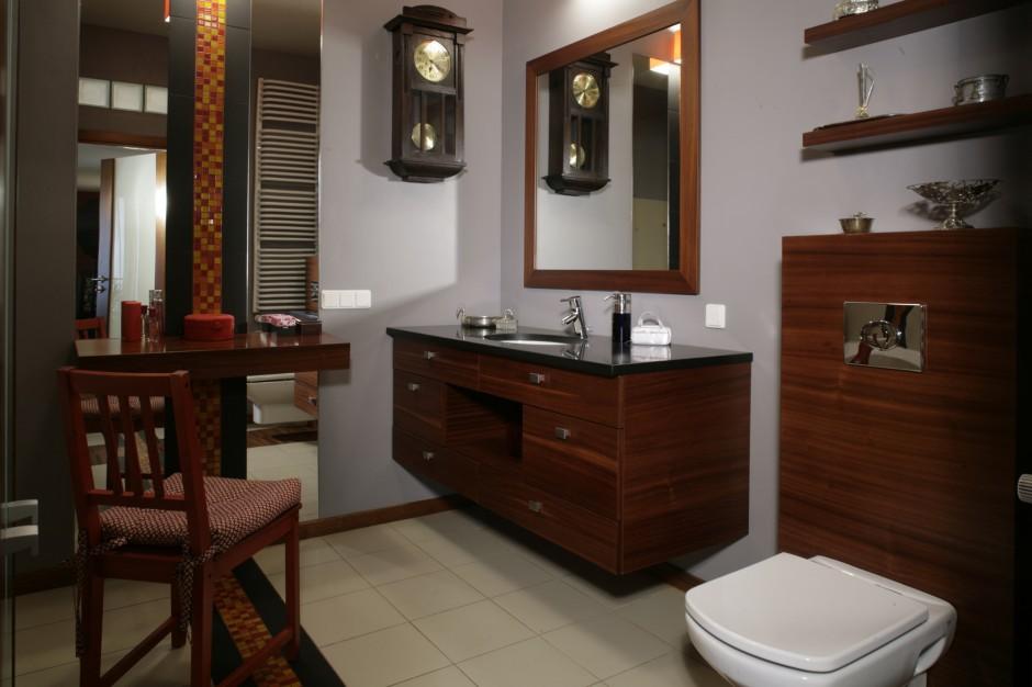 W aranżacji łazienki wyraźnie czuje się estetykę art déco. Obudowa systemu instalacyjnego sedesu, półki nad nim oraz blat toaletki i podumywalkowa szafka wykonane zostały z mahoniu. Fot. Monika Filipiuk.