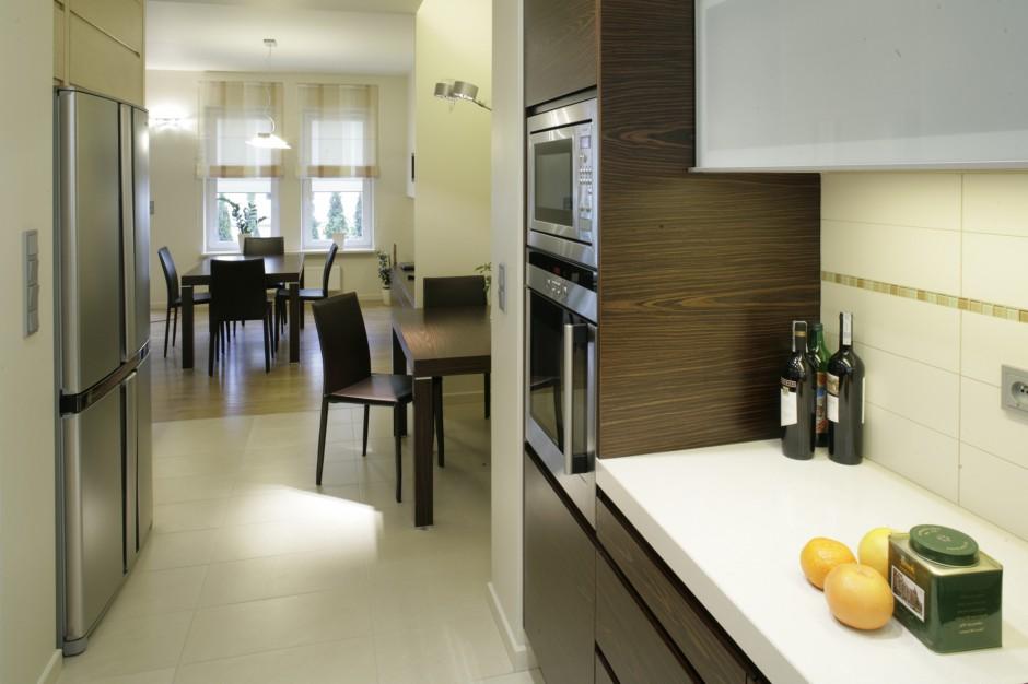 Pokryty hebanowym fornirem stół i ciemne tapicerowane krzesła w aneksie jadalnianym przy kuchni oraz komplet w salonie reprezentują tą samą stylistykę. Różnią się jedynie gabarytami. Fot. Bartosz Jarosz.