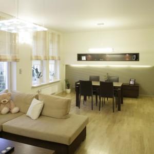 Tłem dla dużego stołu jest podświetlony fragment ściany pokryty czesanym tynkiem przypominającym sztruks. Taka sama ściana pojawia się także za telewizorem w salonie. Fot. Bartosz Jarosz.