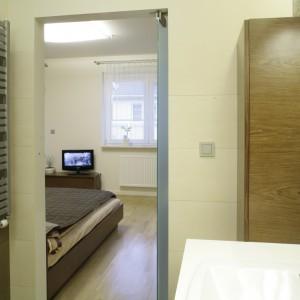 Niewielką przestrzeń między ścianą i umywalką zajęła praktyczna szafka słupek. Sypialnię oświetla lampa przypominająca przyczepiony do sufitu prostokątny kawałek płótna. Fot. Bartosz Jarosz.