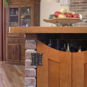 Dopełnieniem ceglanego drink-baru są drewniane drzwi rodem z amerykańskiego saloonu. Kute zawiasy wykonano na zamówienie. Widoczny zza baru -kredens stanowi wyposażenie jadalni. Fot. Monika Filipiuk.
