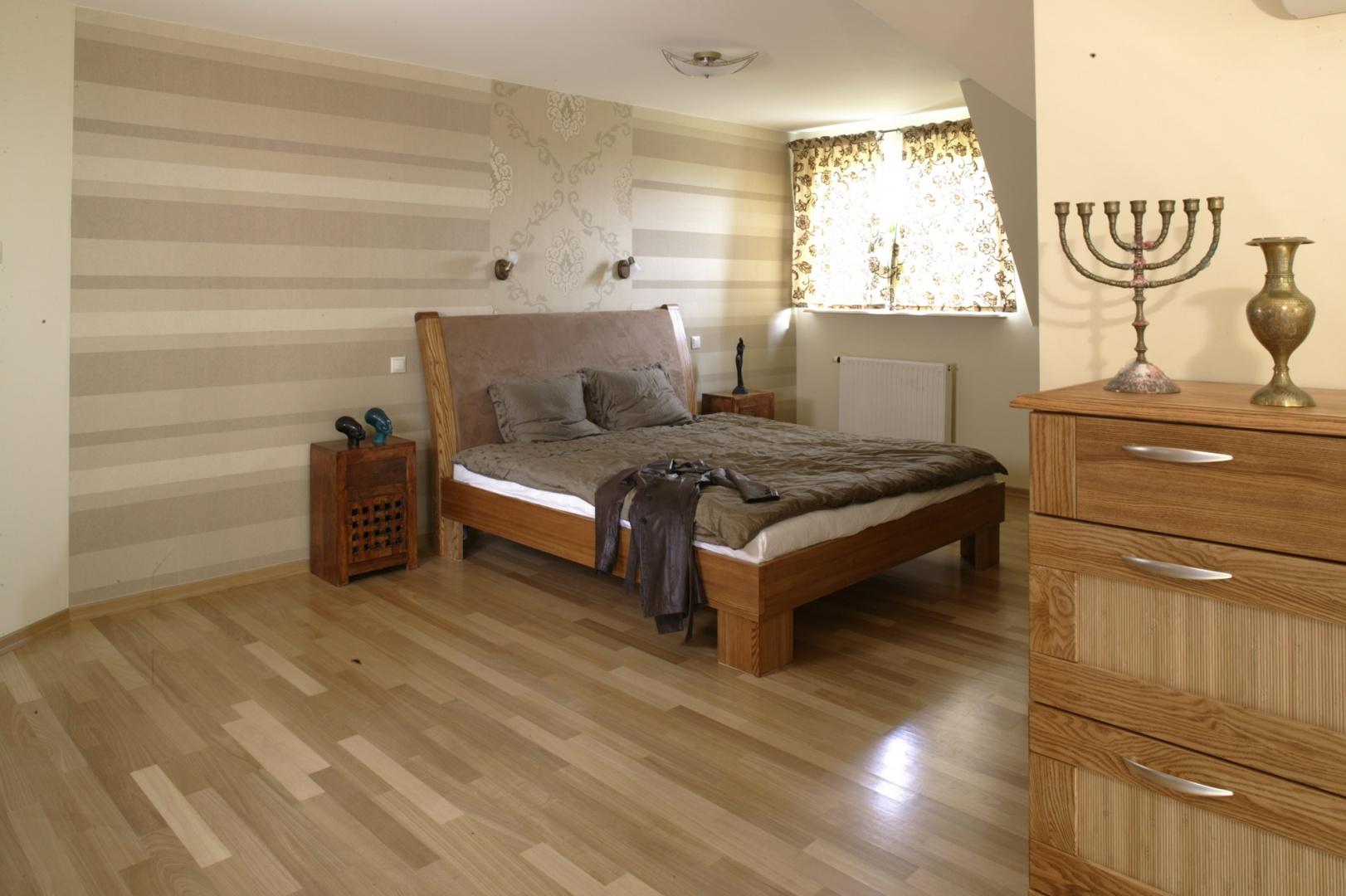 Ściana za łóżkiem ma charakter dekoracyjny. Pokrywają ją dwa rodzaje tapet (Art Funk) w tych samych odcieniach brązu i beżu, ale zróżnicowanych pod względem deseni – poziome pasy i barokowy ornament. Fot. Monika Filipiuk.