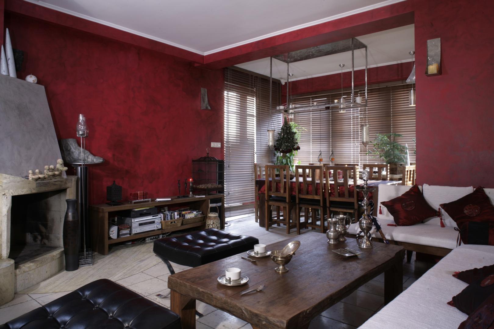 """Salon to wnętrze """"gęste"""" i bogate, zaprzeczenie stylistycznej ascezy. Ściany pokryto tu ciemną, bordową farbą, na której wykonano ręczne przecierki z czarnego lazuru. Oryginalne meble zostały zaprojektowane przez Cezarego Tochmana, ale wykonane... w Chinach. Fot. Monika Filipiuk."""