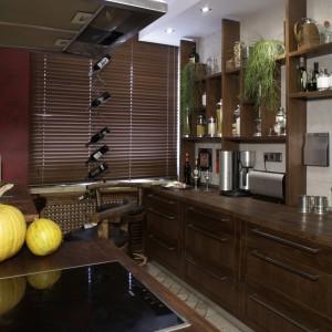 Pozostawiony fragment ściany osłania strefy gotowania i zmywania. Okap i lodówka w kolorze inox bynajmniej nie zakłócą egzotyczno-rustykalnego wizerunku kuchni. Fot. Monika Filipiuk.