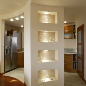 Kuchnia miała być otwarta, ale nieco przesłonięta. Półokrągła ścianka z podświetlanymi, wypełnionymi fakturowanym tynkiem wnękami, w których stoi szkło, stała się efektowną dekoracją salonu. Fot. Monika Filipiuk.