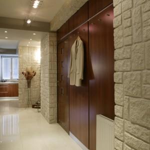 Już w holu mamy zapowiedź kluczowego elementu dekoracyjnego, który będzie przewijał się w całym mieszkaniu. Ścianka wyłożona płytkami imitującymi naturalny kamień, doskonale prezentuje się w świetle halogenów, które eksponują jej ciekawą fakturę. Fot. Monika Filipiuk.