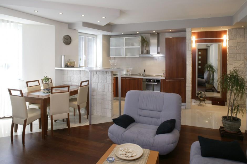 Skosy podwieszanych sufitów, a także dwa rodzaje podłóg, symbolicznie wydzielają strefy: kuchenną i salonową. Fot. Monika Filipiuk.