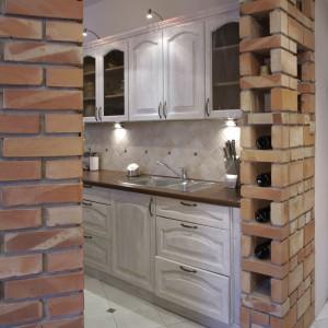 Kuchnia jest otwarta. Dwie stojące naprzeciw siebie ceglane ścianki tworzą jakby kolumny, pomiędzy którymi przechodzi się do jej wnętrza. Fot. Monika Filipiuk.