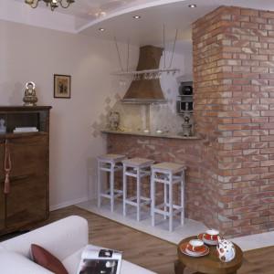 Kuchenną przestrzeń wydzielają niemal biały włoski gres podłogowy i podwieszany nad nią sufit. Stara komoda art déco w salonie koresponduje z utrzymaną w przedwojennym stylu kuchnią. Fot. Monika Filipiuk.