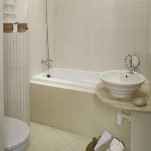 W lekko stylizowanym wnętrzu łazienki dominują jasne kolory ecru i zgaszonego beżu. Ścianę przy grzejniku zdobią małe płaskorzeźby autorstwa projektantki, które doskonale podkreśliły stylistykę wnętrza. Fot. Monika Filipiuk.