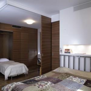 Po przesunięciu dwóch ścianek, z przestrzeni sypialni można wyodrębnić gościnny pokój, z którego korzystają odwiedzający gospodarzy synowie. W ściennej zabudowie schowane są dwa łóżka – można ich używać oddzielnie lub złączone razem. Fot. Monika Filipiuk.