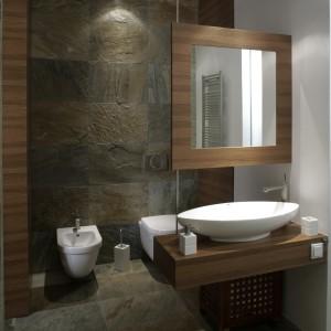 """Łazienka właścicieli została zamieniona w nowoczesną grotę skalną. Niemal w całości pokrywają ją płytki (firma?), o fakturze naturalnego kamienia. W tle strefa WC, symbolicznie wydzielona """"wiszącym"""" lustrem i szafką z umywalką (prod. NIC Design). Fot. Monika Filipiuk."""