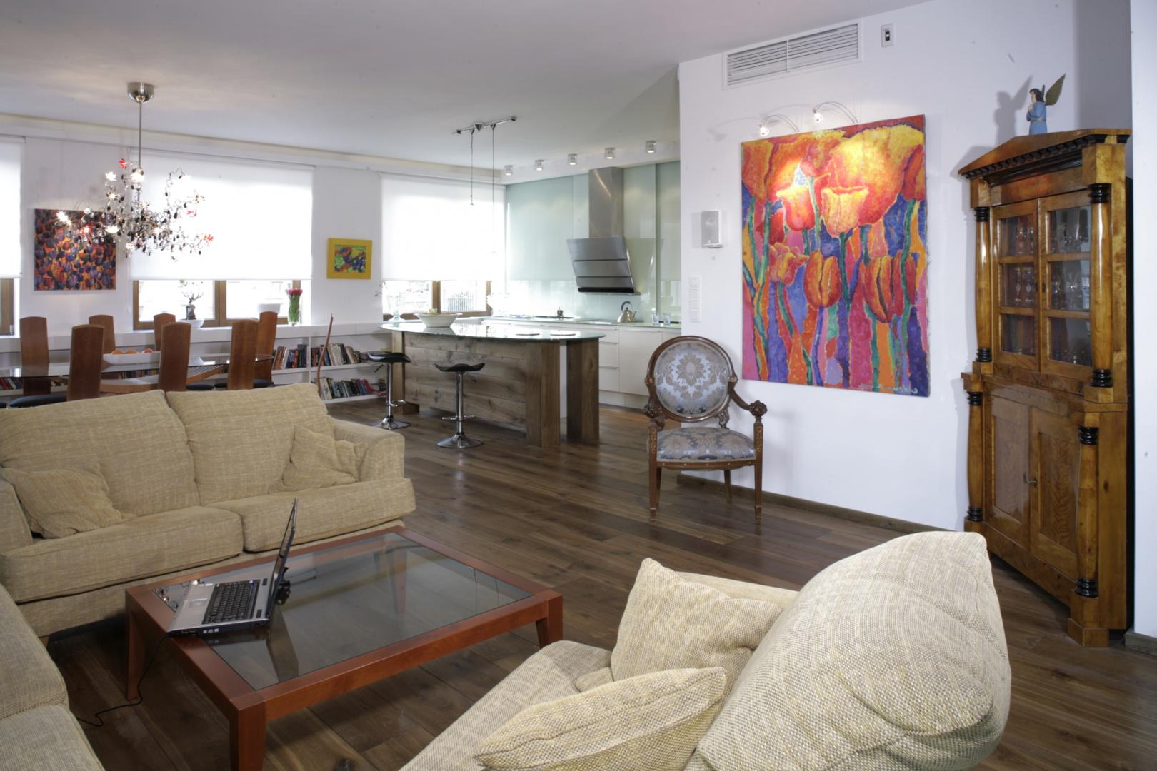 Salon, jadalnia i kuchnia zajmują większą część przestronnego apartamentu. Nowocześnie zaprojektowana przestrzeń została rozdysponowana pomiędzy kącik wypoczynkowy, dosyć sporą jadalnię oraz otwartą kuchnię, urządzoną w high-techowym stylu. Fot. Monika Filipiuk.