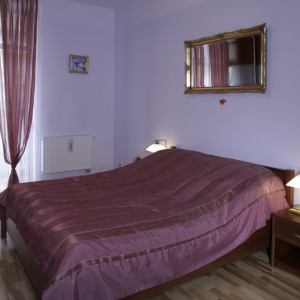 Obszerne łóżko i małe szafki nocne, to główne meble w sypialni. Wrzosy i fiolety dodają wnętrzu romantyzmu. Fot. Monika Filipiuk.