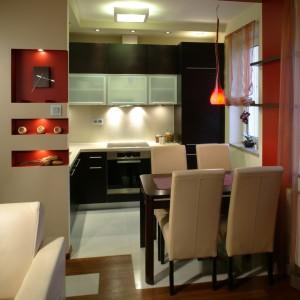 Wnękowe, dekoracyjne półki w ścianie dzielącej kuchnię od łazienki zostały dodatkowo podświetlone – wieczorem pełnią funkcję nastrojowej lampki. Wewnątrz jednej z nich widać zegar. Fot. Bartosz Jarosz.