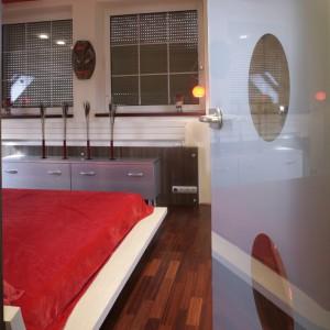 Trzy tonacje kolorystyczne współzawodniczą ze sobą o uwagę użytkowników sypialni. Pierwszy to   odcień drewna, pojawiającego się na ścianach i podłodze. Drugi to mocny, śmiały akcent - soczysta   czerwień na suficie. Ostatnim, jest kolor srebrzystostalowy, wprowadzony tu za sprawą niebanalnej   komody z laminatu.  Fot. Monika Filipiuk.