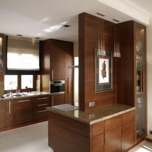 Zabudowa na pograniczu kuchni i jadalni jest zarazem dekoracyjna i funkcjonalna. W przeszklonej szafie jest miejsce na szkło użytkowe, w szufladach – na wszelkie akcesoria. Granitowy blat to jednocześnie barek. Fot. Bartosz Jarosz.