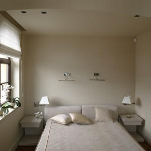 """Gościnna sypialnia to pokój przytulny i niezwykle wygodny. Przestronne łoże z tapicerowanym wezgłowiem, dwie nocne szafeczki, a nawet lampki na ścianie, wprost stworzone do nocnego """"pochłaniania"""" książek – klimat sprzyjający wyjątkowo długiemu relaksowi. Fot. Bartosz Jarosz."""