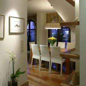 """Podłogę w części dziennej mieszkania pokrywają orzechowe deski. W przedpokoju gresowe płyty (Irys) skomponowano z wąskim trawertynowym pasem, który z """"wkrada się"""" również do kuchni i łazienki. Fot. Bartosz Jarosz."""