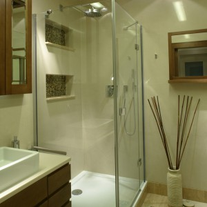 Łazienka gospodarzy wyposażona została w przeszkloną kabinę prysznicową. W podłodze i ścianie umieszczono wstawki z kamyków zatopionych w żywicy (Irys). Fot. Bartosz Jarosz.