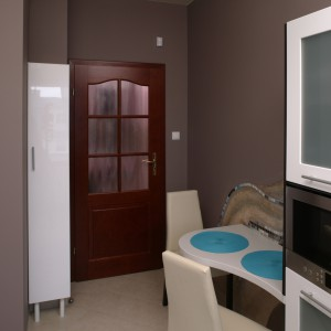 Kuchnia jest osobnym, zamykanym drzwiami wnętrzem. Najbliżej wejścia znajduje się stolik śniadaniowy w formie wyokrąglonego blatu i wygodne, tapicerowane krzesła. Fot. Bartosz Jarosz.