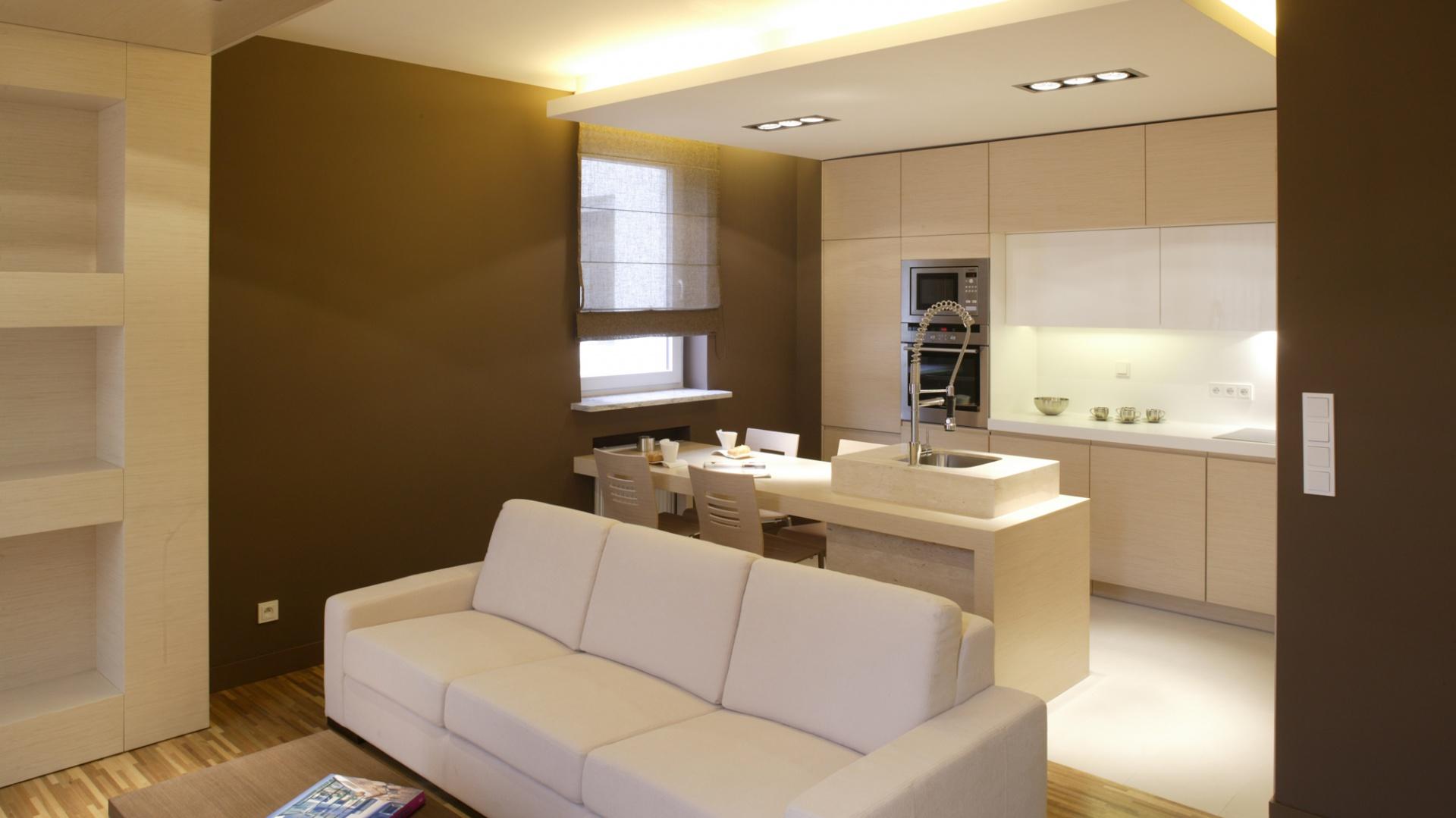 Obniżony sufit optycznie domyka pudełkową konstrukcję wnętrza. Półprzejrzysta, o czekoladowej barwie roleta w oknie nie burzy koncepcji dużych, jednolitych powierzchni. Fot. Bartosz Jarosz