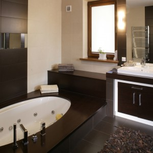 Ta część łazienki to miejsce służące przede wszystkim relaksowi. Sprzyja mu nie tylko kąpiel w wannie z hydromasażem, ale i jej cała aranżacja – elegancka, a jednocześnie przytulna i ciepła. Fot. Monika Filipiuk.