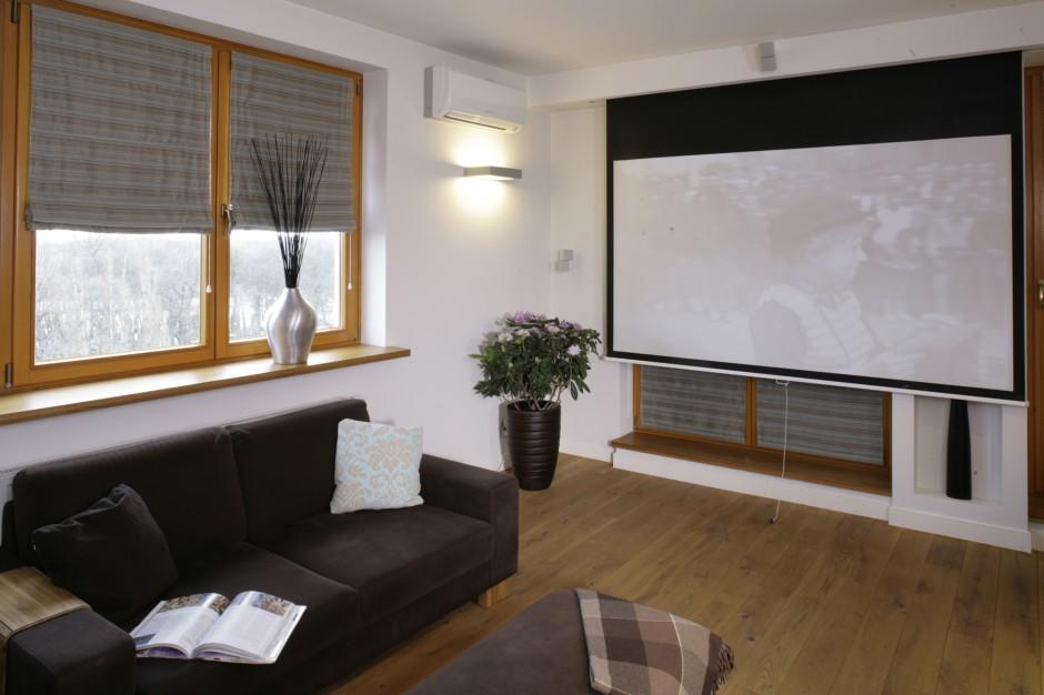 Gospodarze są wielkimi miłośnikami kina, a równocześnie domatorami. Dlatego też salon wyposażyli w ogromny ekran, który zamienia wnętrze w prywatną salę kinową. O jej klimat dbają drewniane akcenty – ramy okien i podłoga, wyłożona olejowanymi deskami tekowymi.