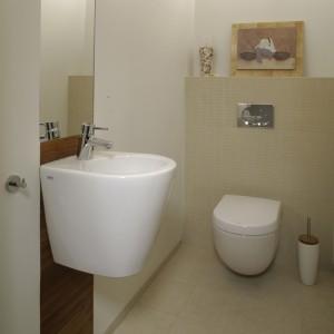 Nad umywalką (Keramag, armatura Oras) w gościnnym WC umieszczono pionową taflę lustra, która optycznie poszerza niewielkie wnętrze. Goszczą w nim drewno tekowe i kremowy gres o fakturze kamienia, oraz mozaika pokrywająca ścianę za sedesem.