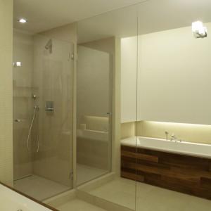 Kabina prysznicowa w łazience znalazła się pomiędzy wanną a ogromnym lustrem, pokrywającym jedną ze ścian. Lustro wywołuje optyczne złudzenie przestrzeni, co doskonale sprawdza się w wąskim i długim wnętrzu.
