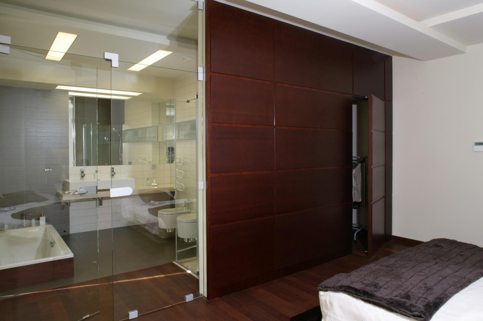 Salon kąpielowy jest przedłużeniem małżeńskiej sypialni. Oba wnętrza dzieli ściana ze szkła. Jej częścią są otwierane w dwie strony drzwi do łazienki. Fot. Monika Filipiuk.