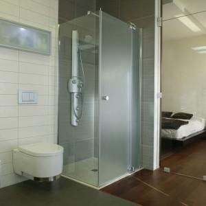 Zainstalowana w narożniku łazienki szklana kabina prysznicowa z panelem natryskowo-masażowym jest z sypialni praktycznie niewidoczna. Fot. Monika Filipiuk.